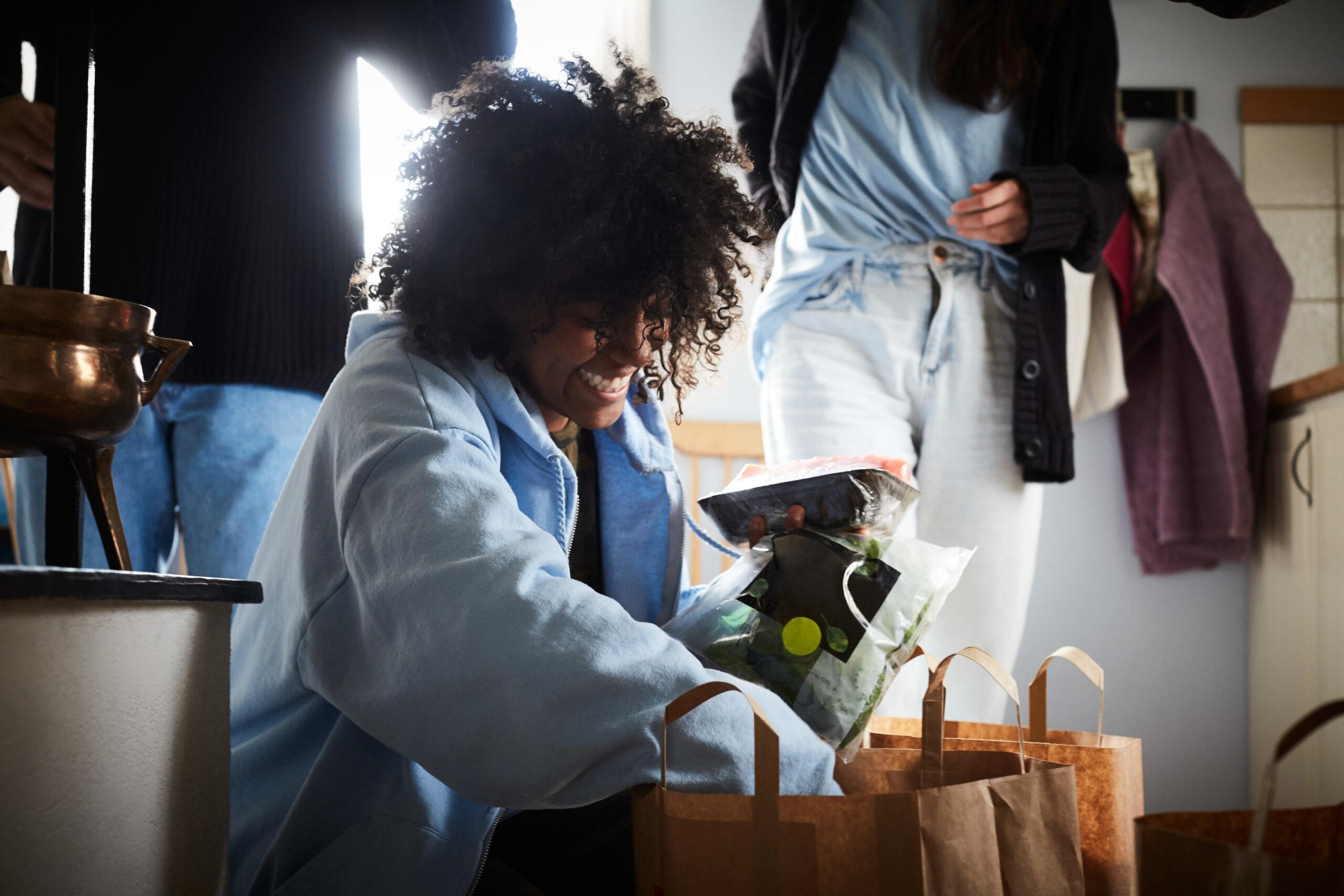 Kvinna plockar upp sallad och andra matvaror ur papperskassar. Förpackningsmaterialets inverkan på maten.