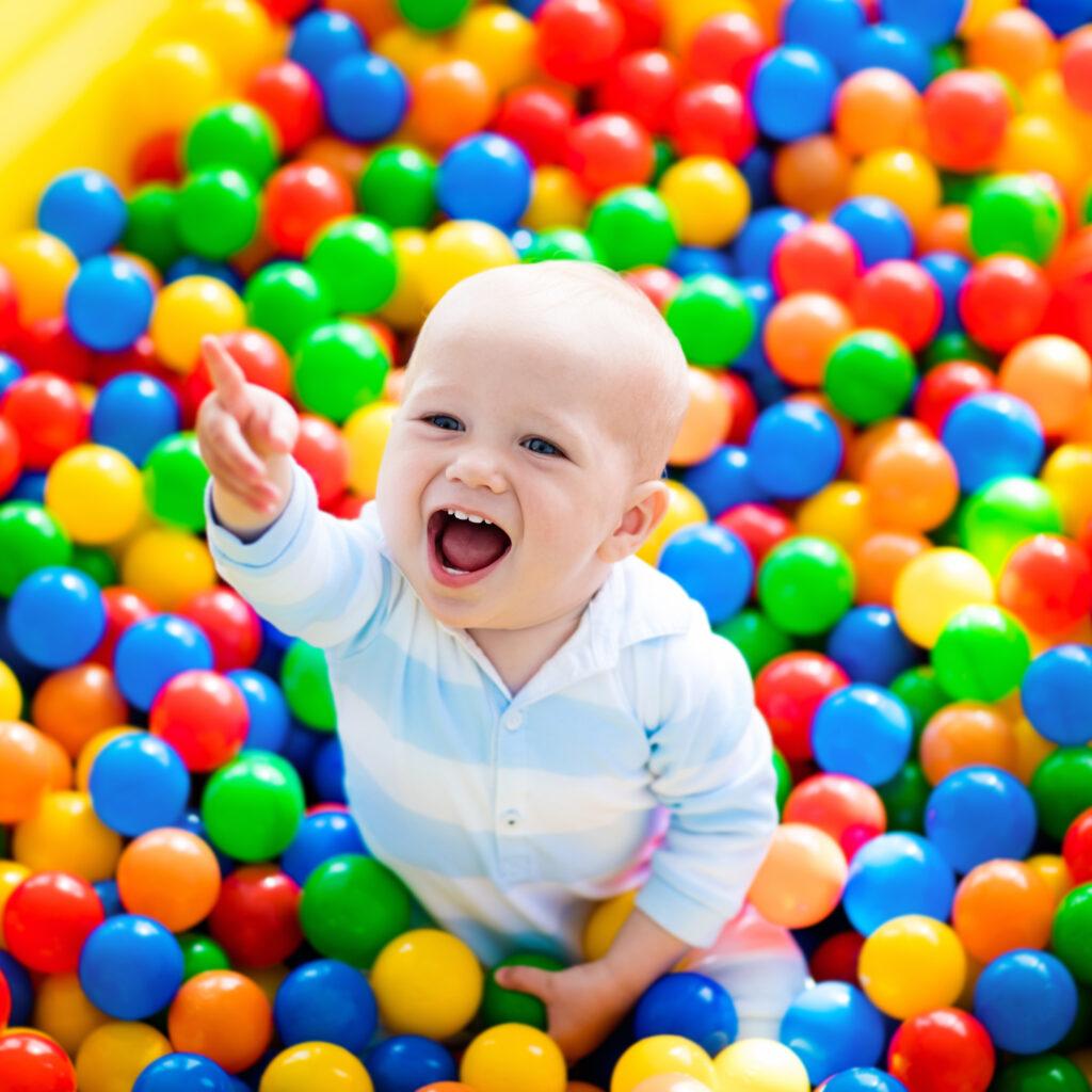 Glad pojke leker med färggranna bollar i ett bollhav. Operation giftfri förskola. Tillsammans avgiftar vi barnens vardag.