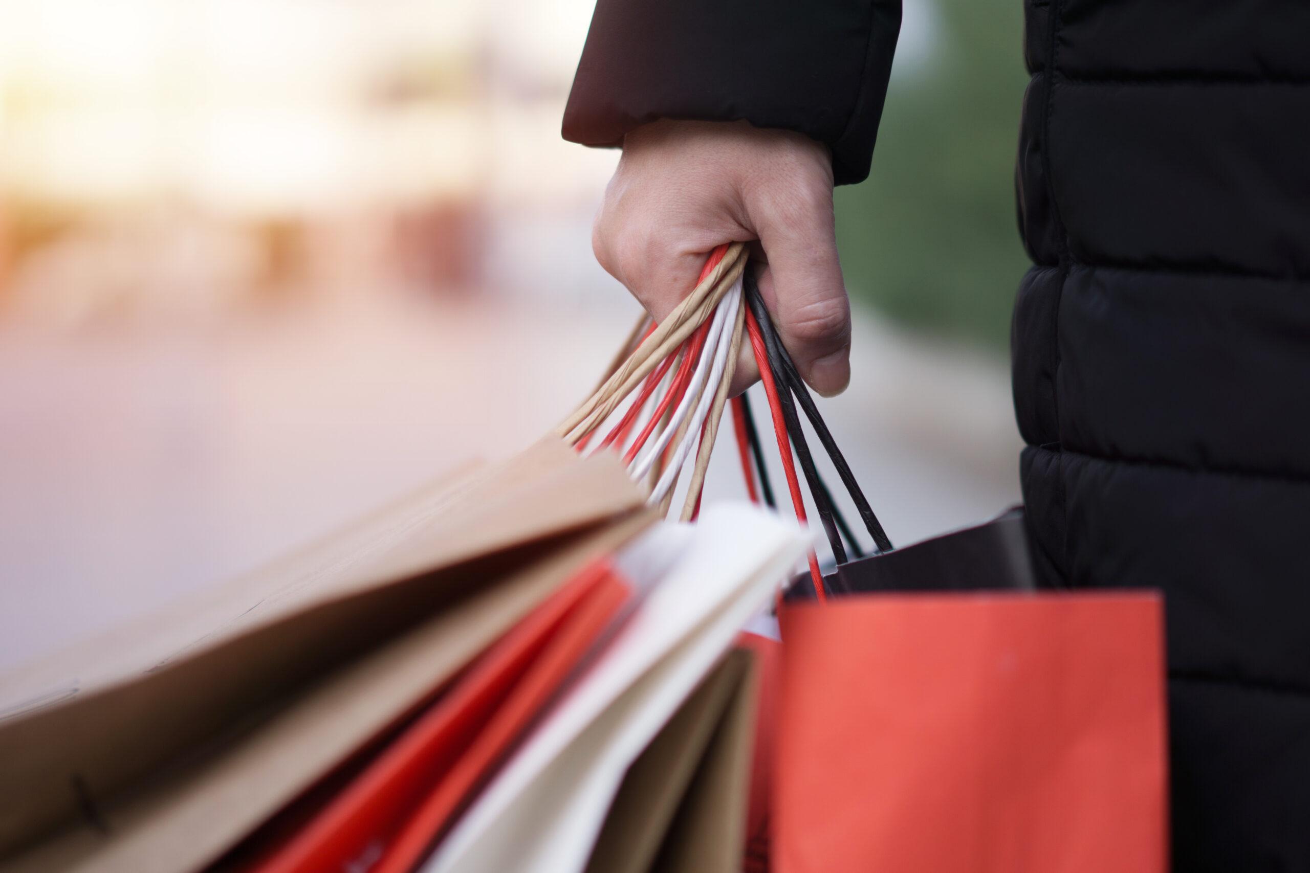 Hand med shoppingkassar