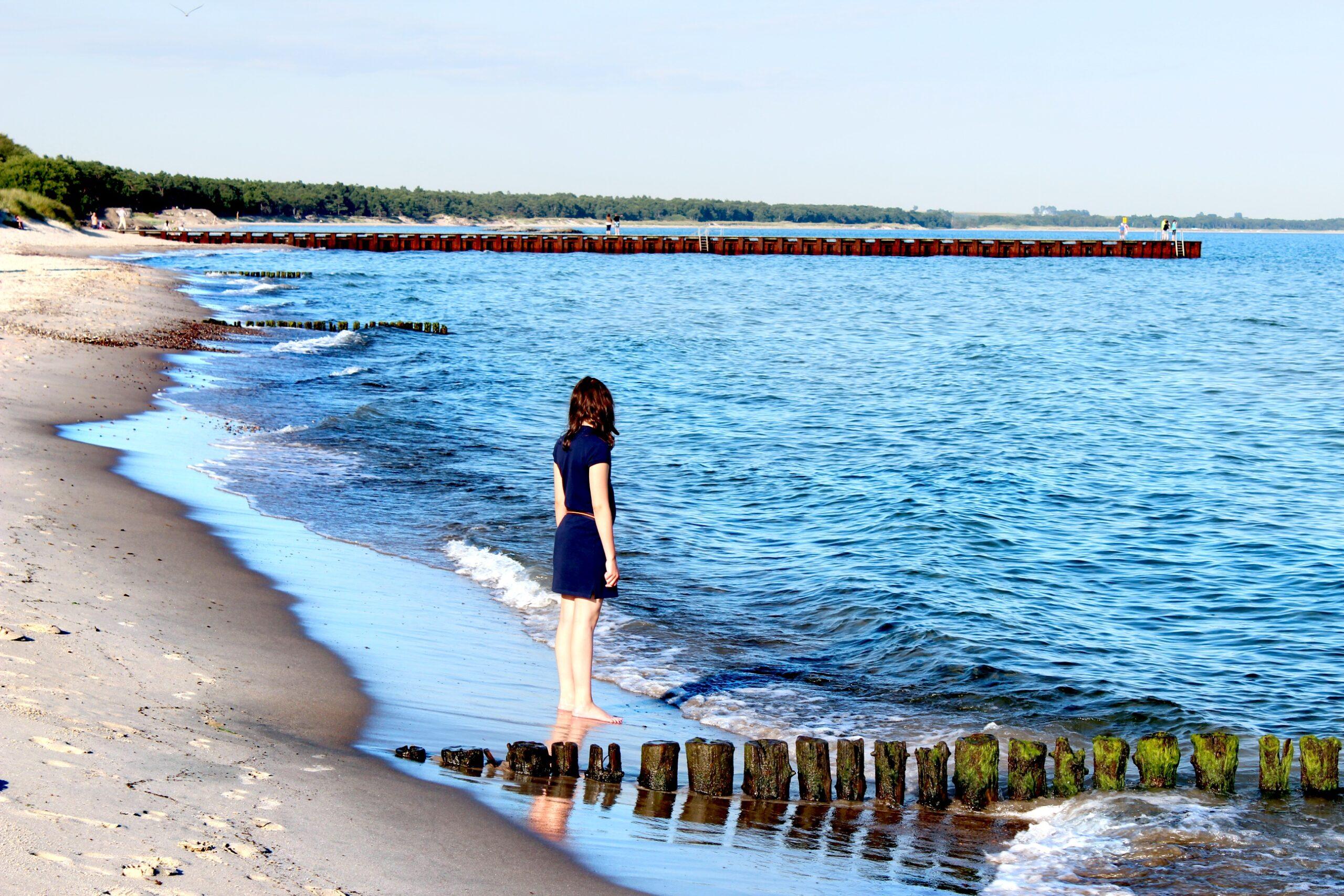 Så påverkas haven av klimatförändringar. En ensam flicka på en strand blickar ut över havet.