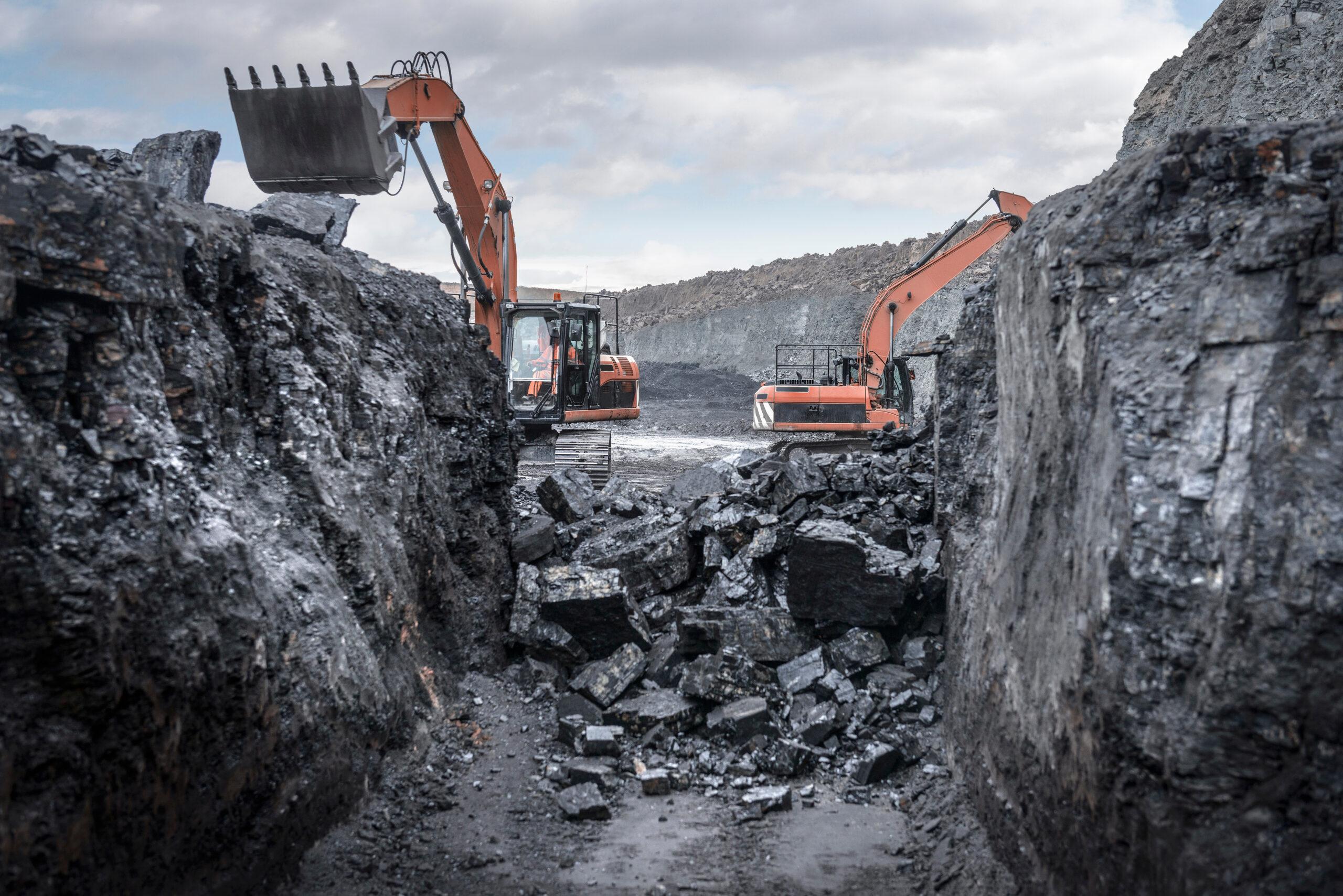 Grävmaskiner gräver ut kol.
