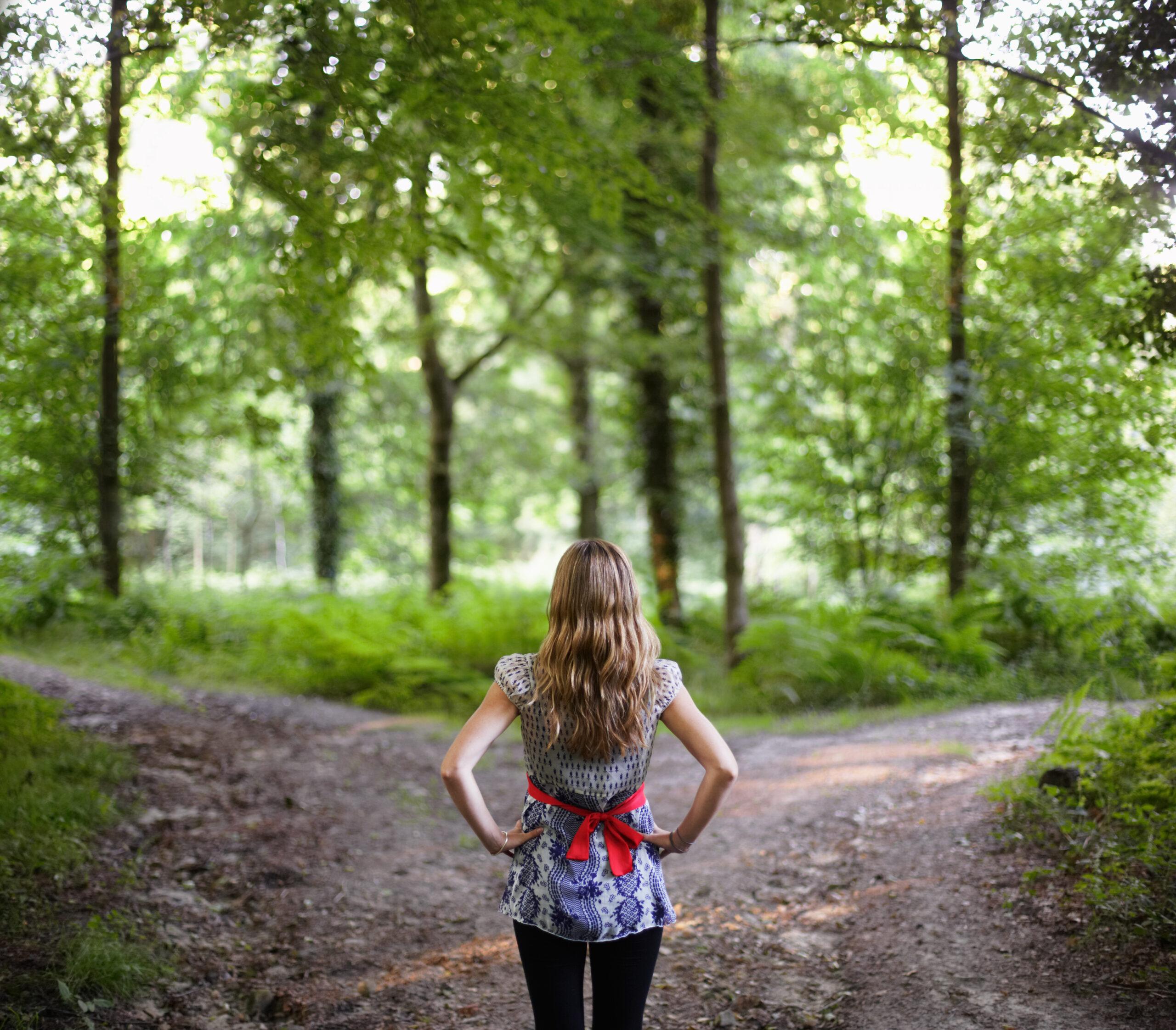 tjej gör val vid väg i skog