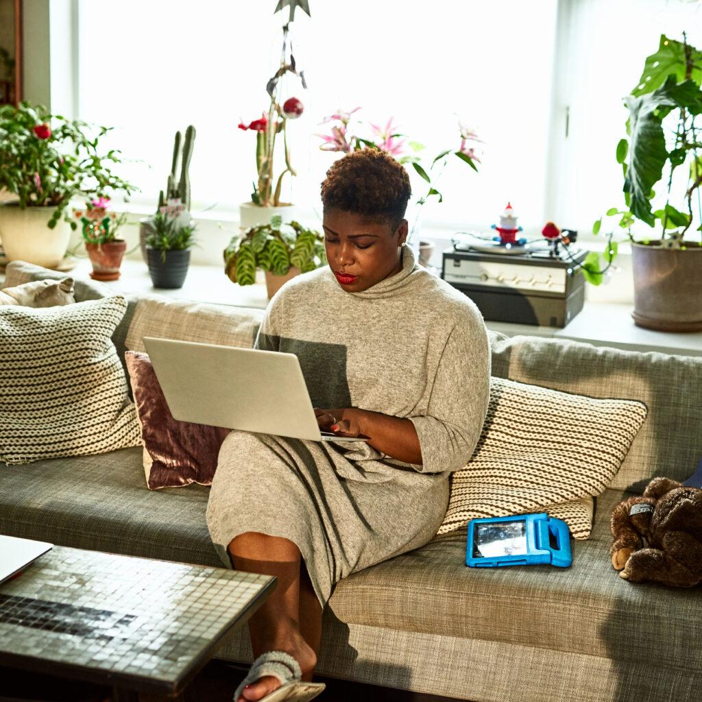 Kvinna sitter med dator i knät. Bli digital aktivist från soffan.