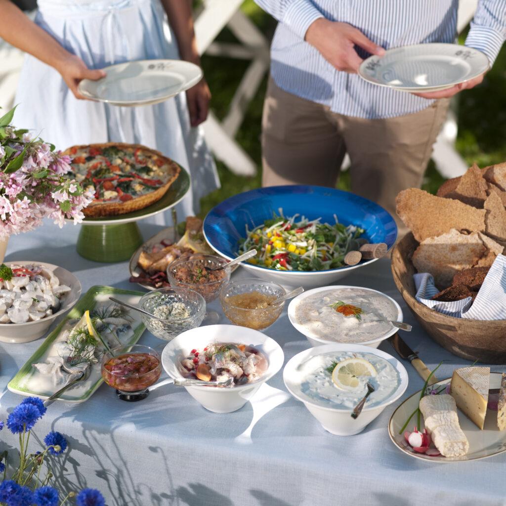 njutning, tradition, två personer, lycka, fritidskläder, tallrik, samhörighet, ung vuxen man, ung vuxen kvinna, vy ovanifrån, buffé, sallad, grönsak, dagtid, stående, sommar, ost, 20-24 år, optimism, utomhus, paj, sill, knäckebröd, skål, Sverige, frukt och grönsaker, fest, bord, sommarmat, svensk tradition.