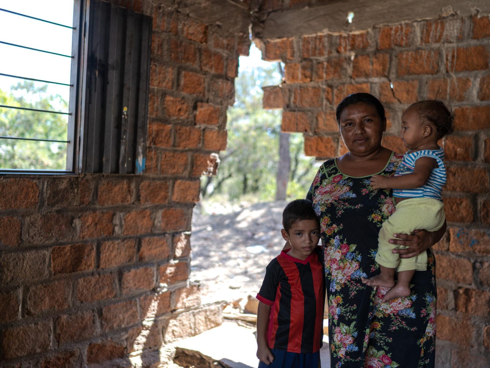 Luz Angela Uriana står i sitt hus med sin son Moises Guette och sin dotter Saray Guette. De dagliga gruvsprängningarna har gjort att en del av husväggen har rasat.
