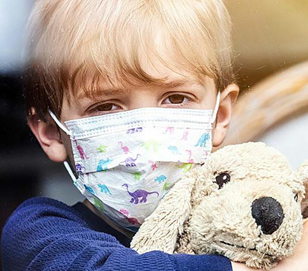 Pojke med munskydd och gosedjur