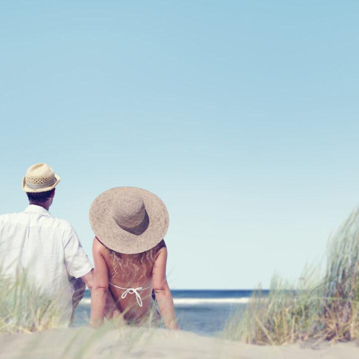 Kvinna och man sitter på en strand
