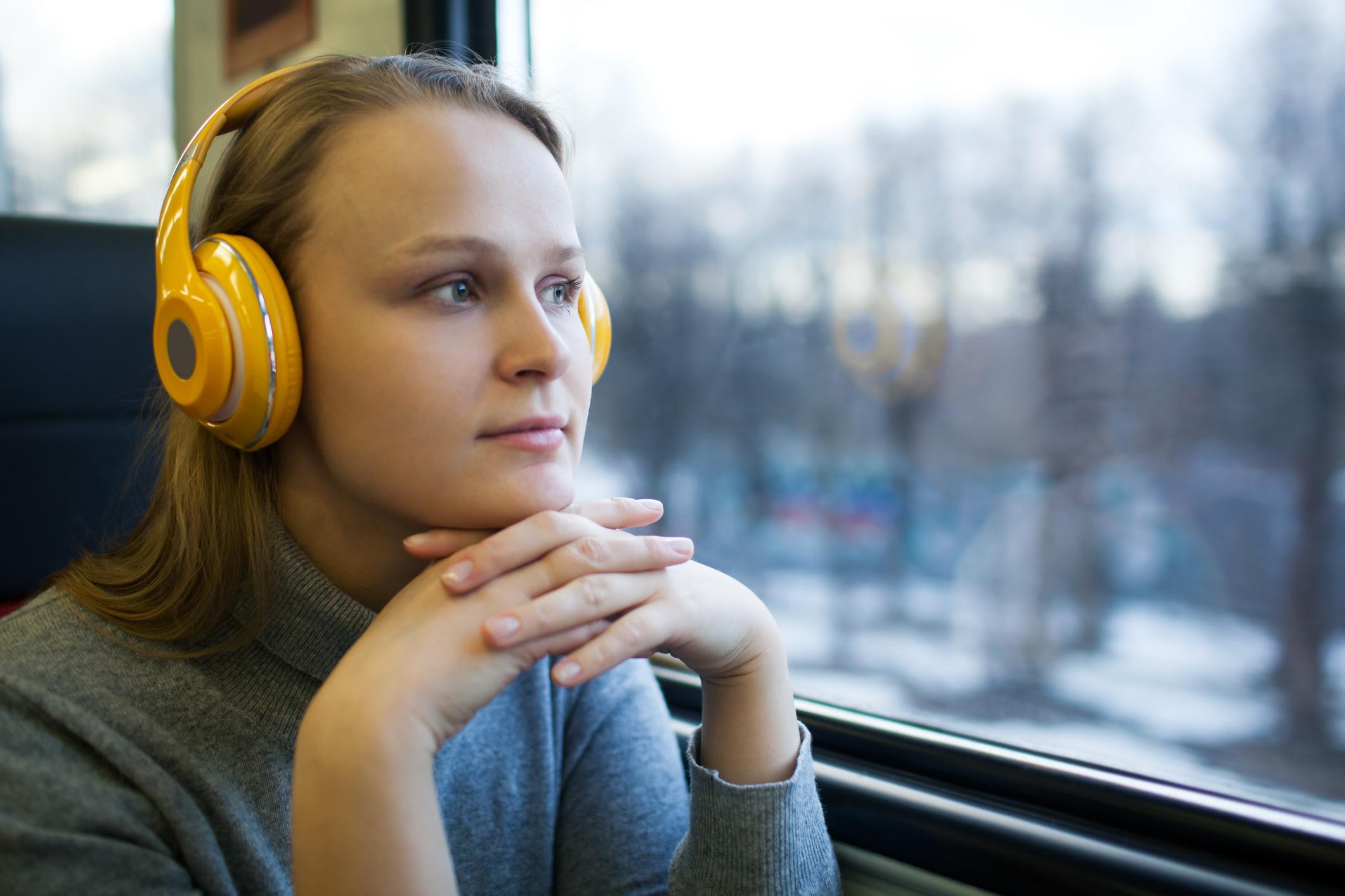 Ung kvinna ser ut genom tågfönster.